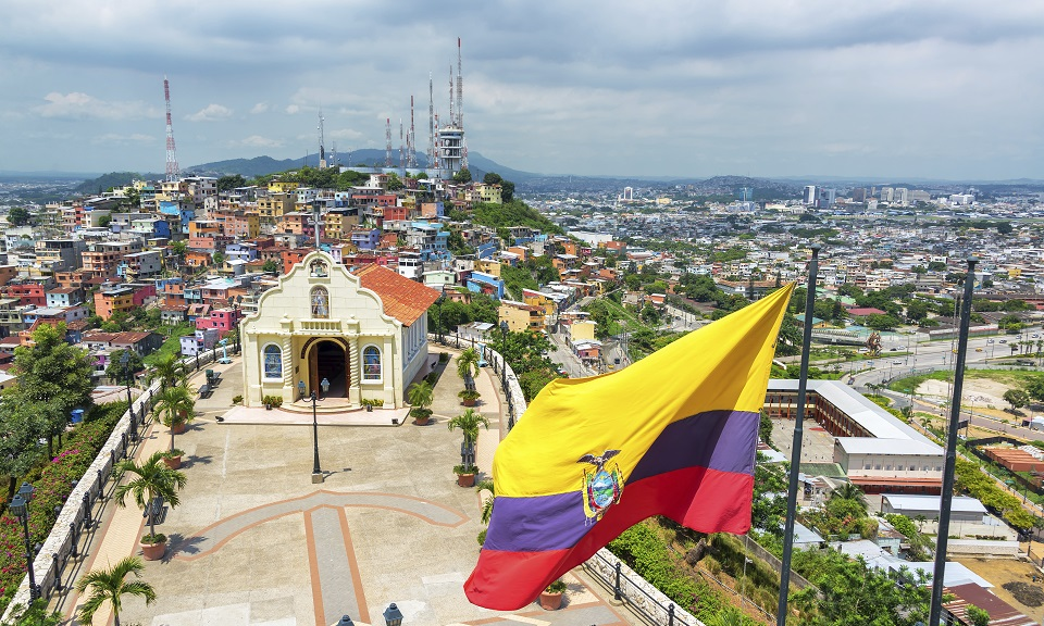 Ecuadorian flag on top of Santa Ana hill with a church and the city of Guayaquil visible in the background in Ecuador