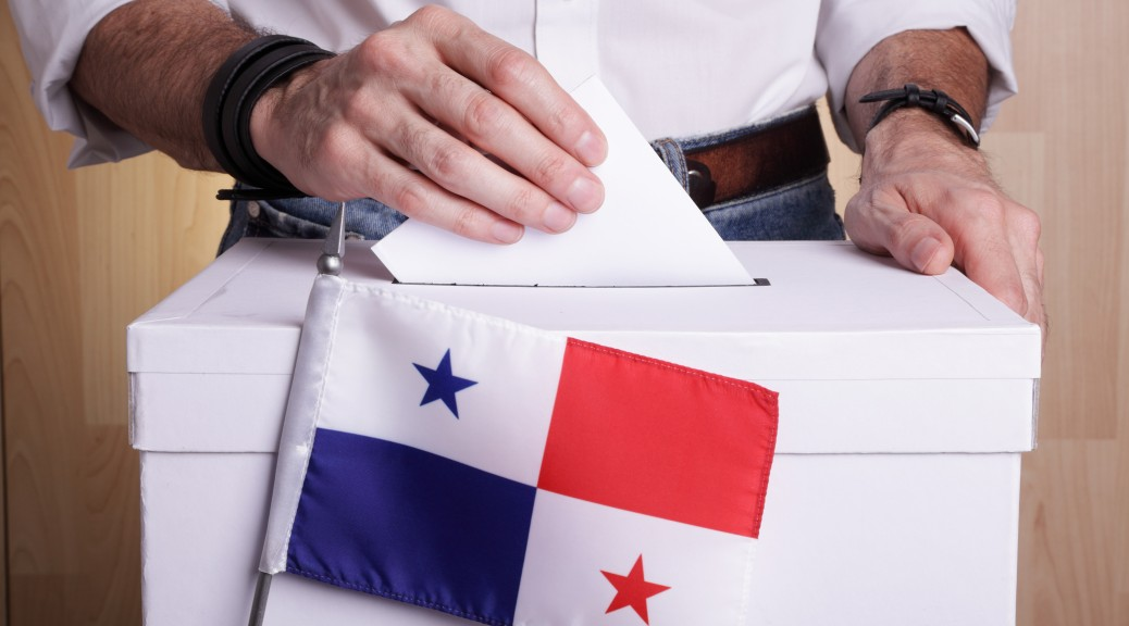 A man inserting a ballot to a ballot box.  Panamanian flag in front of it.
