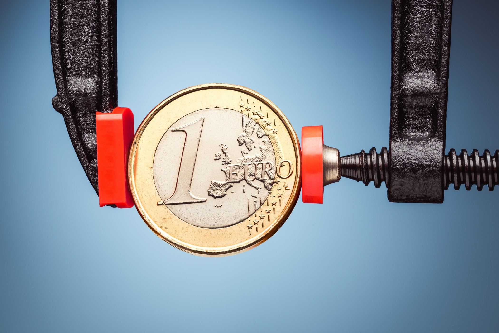 One Euro coin under pressure. Crisis concept.