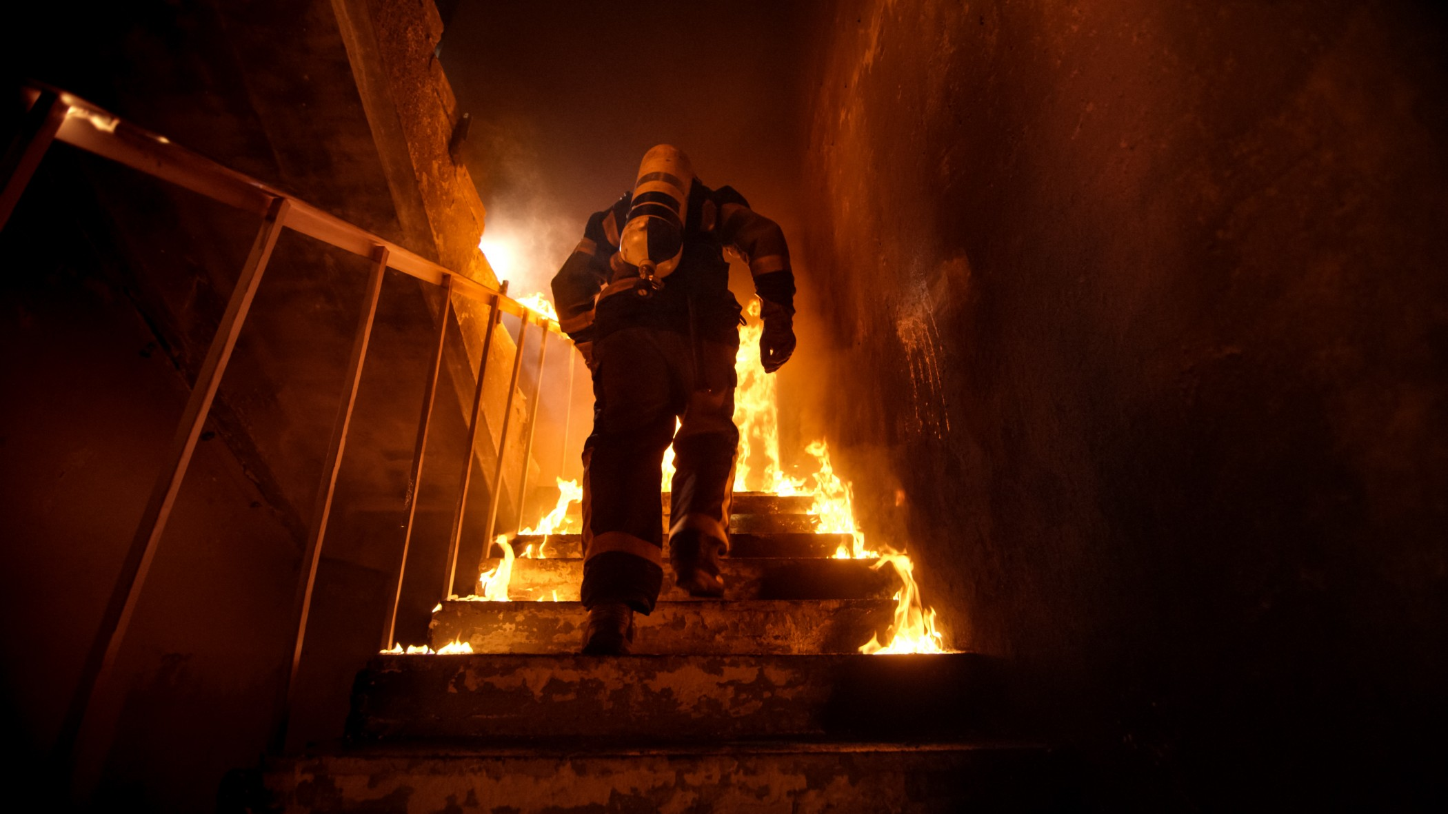 Strong and brave Firefighter Going Up The Stairs in Burning Building. Stairs Burn With Open Flames.