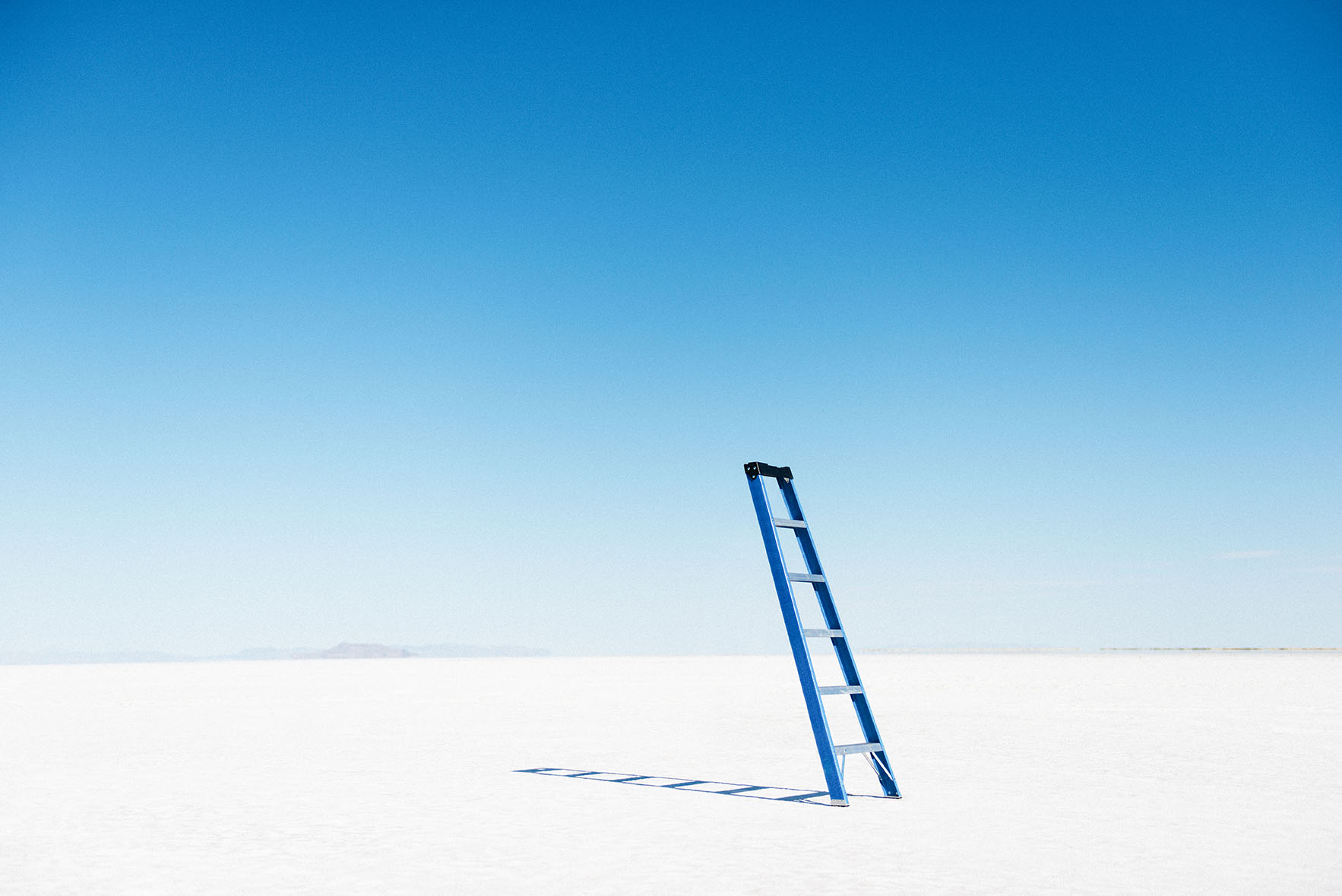 Blue ladder balanced in the middle of the desert. Stairway to heaven